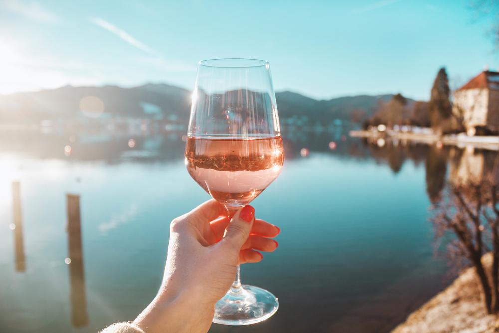 """""""Immagine di un calice di rosato con sfondo panoramico di un lago"""""""